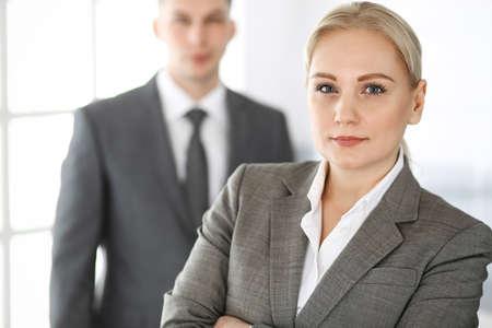 Donna d'affari in piedi dritto con un collega uomo d'affari in ufficio, colpo alla testa. Successo e concetto di partnership aziendale