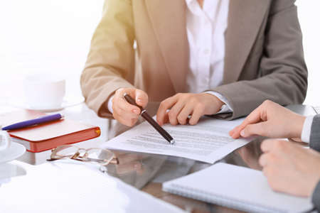 Group of business people or lawyers discussing contract papers sitting at the table, close-up
