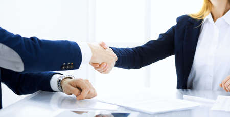 Business people shaking hands finishing up a meeting , close-up. Success at negotiation and handshake concepts. Group of lawyers at work.