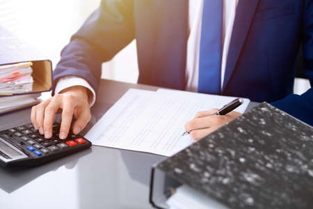 Bookkeeper or financial inspector hands making report, calculating or checking balance. Internal Revenue Service inspector man checking financial document. Business, tax and audit concepts.