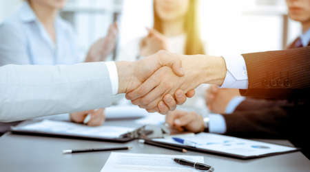 Business people shaking hands at meeting while theirs colleagues clapping and applausing. Group of unknown businessmen and women in modern white office. Success teamwork, partnership and handshake concept.
