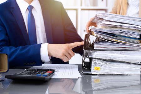 Comptable ou inspecteur financier et secrétaire faisant un rapport, calculant ou vérifiant le solde. Inspecteur de l'Internal Revenue Service vérifiant le document financier. Notion de vérification.