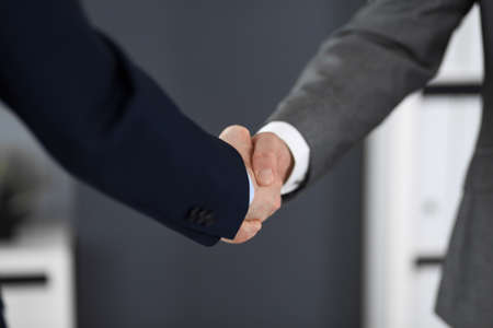 Business people shaking hands at meeting or negotiation, close-up. Group of unknown businessmen and women in modern office. Teamwork, partnership and handshake concept.