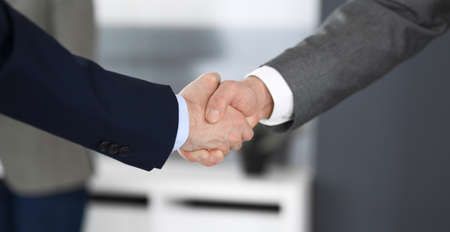 Business people shaking hands at meeting or negotiation in modern office, close-up. Teamwork, partnership and handshake concept. Imagens - 121623814