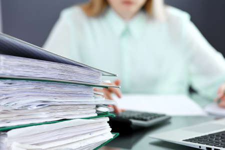 Bookkeeper or financial inspector  making report, calculating or checking balance. Audit and tax service concept. Green colored image background.
