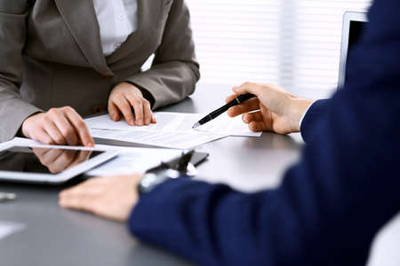 Business people and lawyer discussing contract papers sitting at the table, hands close-up. Teamwork or group operations concept.