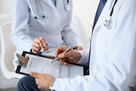 Two unknown doctors filling up medical form on clipboard, just hands closeup. Physicians asking question to patient or discussing medication program. Healthcare, insurance and medicine concept.