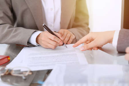 Businesswoman signing contract papers. Group of business people at meeting or negotiation, close-up