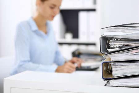 Ordner mit Papieren warten darauf, von Geschäftsfrau oder Buchhalterin wieder verschwommen bearbeitet zu werden. Interne Revision und Steuerkonzept Standard-Bild