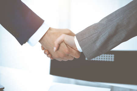 Businessman and business woman shaking hands to each other above signed contract. Success at negotiation and agreement  concept Imagens - 121934832