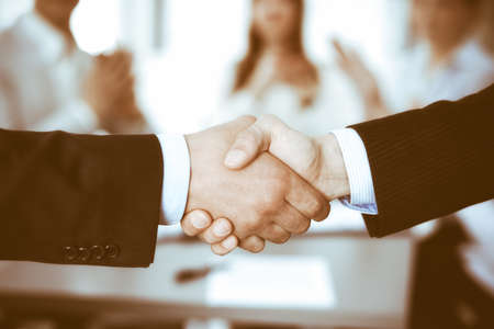 Business people shaking hands at meeting while theirs colleagues clapping and applauding. Group of unknown businessmen and women in modern white office. Success teamwork, partnership and handshake concept Imagens - 121934944