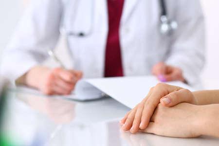 Donna medico sconosciuta che consulta il paziente durante la compilazione di un modulo di domanda alla scrivania dell'ospedale. Solo mani ravvicinate. Concetto di medicina e assistenza sanitaria