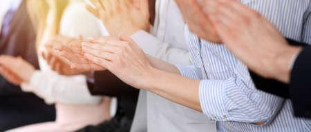 Mensen uit het bedrijfsleven klappen en applaus tijdens vergadering of conferentie, close-up van handen. Groep onbekende zakenlieden en vrouwen in modern wit kantoor. Succes teamwork of corporate coaching concept