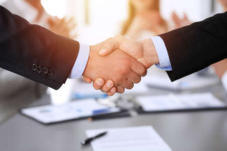 Business people shaking hands at meeting while theirs colleagues clapping and applauding. Group of unknown businessmen and women in modern white office. Success teamwork, partnership and handshake concept Imagens - 121934969