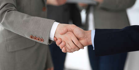 Business people shaking hands at meeting or negotiation, close-up. Group of unknown businessmen and women in modern office at background. Teamwork, partnership and handshake concept Imagens - 121935232