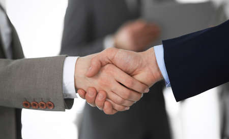Business people shaking hands at meeting or negotiation, close-up. Group of unknown businessmen and women in modern office at background. Teamwork, partnership and handshake concept Imagens - 121935233