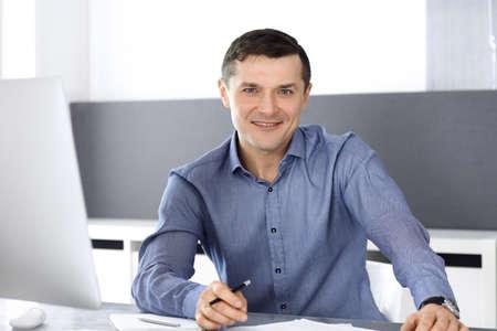 Fröhlicher lächelnder Geschäftsmann, der mit Computer im modernen Büro arbeitet. Kopfschuss eines männlichen Unternehmers oder Direktors eines Unternehmens am Arbeitsplatz. Geschäftskonzept