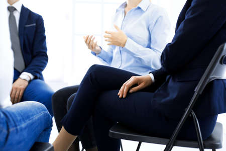 Group of people sitting in a circle during therapy. Meeting of business team participating in training