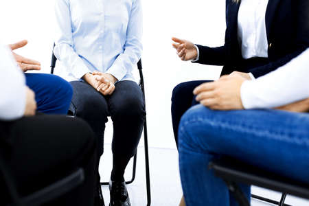 Group of people sitting in a circle during therapy. Meeting of business team participating in training.