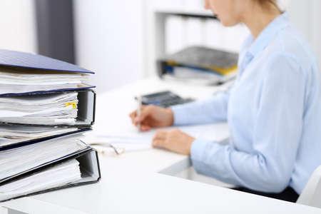 La calculadora y las carpetas con papeles están a la espera de ser procesados por una mujer de negocios o un contable en forma borrosa. Concepto fiscal y de auditoría interna.
