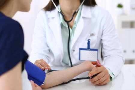 Unbekannte Arztfrau, die den Blutdruck einer Patientin überprüft, Nahaufnahme. Kardiologie in Medizin und Gesundheitskonzept.
