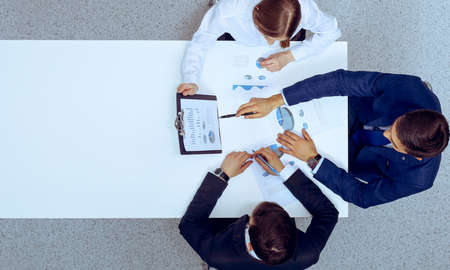 Group of business people analyzing financial documents, view from above. Business team at meeting.