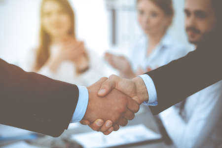 Business people shaking hands at meeting while theirs colleagues clapping and applausing. Group of unknown businessmen and women in modern white office. Success teamwork, partnership and handshake concept. Imagens - 122429242