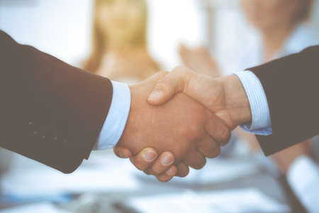 Business people shaking hands at meeting while theirs colleagues clapping and applausing. Group of unknown businessmen and women in modern white office. Success teamwork, partnership and handshake concept. Imagens - 122429253