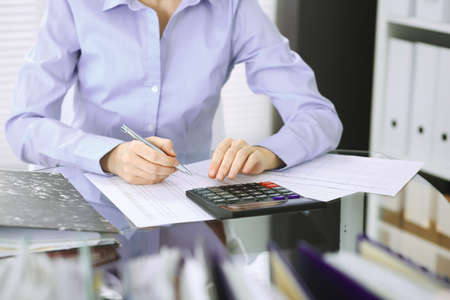 Unknown bookkeeper woman or financial inspector making report, calculating or checking balance, close-up. Business portrait. Audit or tax concepts.