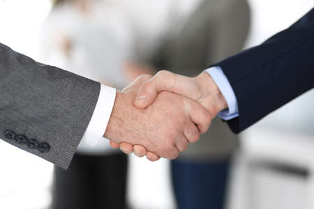 Business people shaking hands at meeting or negotiation, close-up. Group of unknown businessmen and women in modern office at background. Teamwork, partnership and handshake concept.