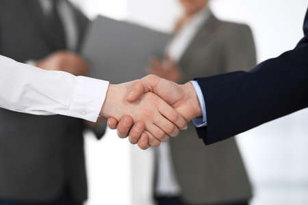 Business people shaking hands at meeting or negotiation, close-up. Group of unknown businessmen and women in modern office at background. Teamwork, partnership and handshake concept. Imagens - 122429450