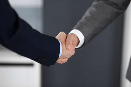 Business people shaking hands at meeting or negotiation, close-up. Group of unknown businessmen and women in modern office. Teamwork, partnership and handshake concept. Imagens - 122429480