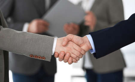 Business people shaking hands at meeting or negotiation, close-up. Group of unknown businessmen and women in modern office at background. Teamwork, partnership and handshake concept. Imagens - 122429545