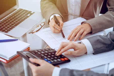 Zwei Buchhalterinnen, die auf Taschenrechnereinkommen für die Ausfüllung des Steuerformulars zählen, Hände Nahaufnahme. Geschäfts- und Prüfungskonzept
