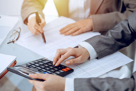 Two female accountants counting on calculator income for tax form completion hands close-up. Business and audit concept