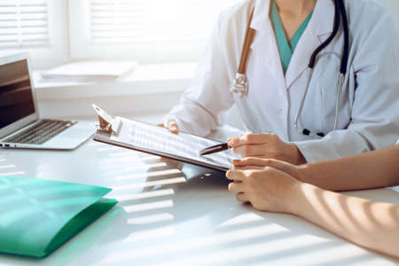 Doctor and patient are discussing something in clinic, just hands at the desk. Medicine and best service concept Stockfoto