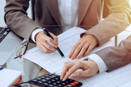 Due ragionieri femminili che contano sul reddito della calcolatrice per il completamento del modulo fiscale passa il primo piano. Business e concetto di audit