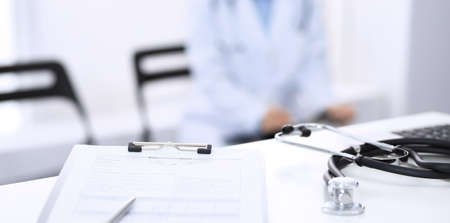 Stethoscope, clipboard with medical form lying on hospital reception desk with laptop computer and busy doctor and patient communicating at the background. Medical tools at doctor working table.Medicine concept Фото со стока