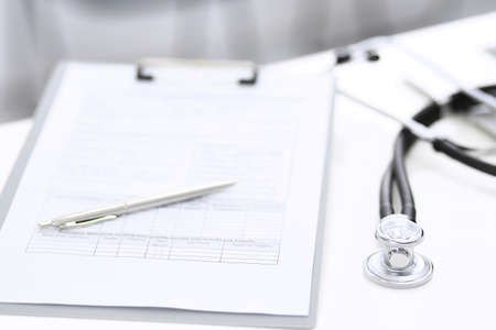 Stethoscope, clipboard with medical form lying on hospital reception desk with laptop computer and busy doctor and patient communicating at the background. Medical tools at doctor working table.Medicine concept Stockfoto