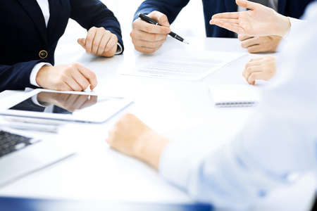 Group of business people and lawyers discussing contract papers sitting at the table, close-up. Successful teamwork, cooperation and agreement concepts