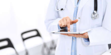 Female physician using digital tablet  while standing near reception desk at clinic or emergency hospital. Unknown doctor woman at work. Medicine concept Stockfoto