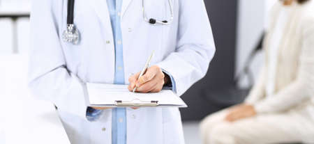 Doctor woman filling up medical form while standing near reception desk at clinic or emergency hospital.Unknown physician at work, hands close-up. Medicine and healthcare concept