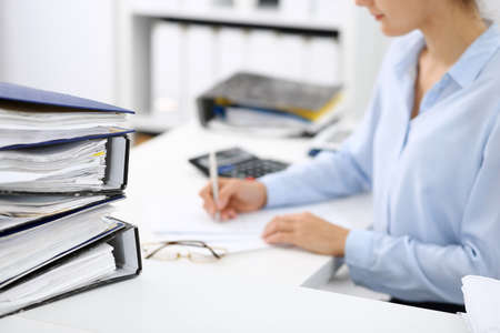 Binders with papers are waiting to be processed by business woman or bookkeeper back in blur. Internal Audit and tax concept Stockfoto