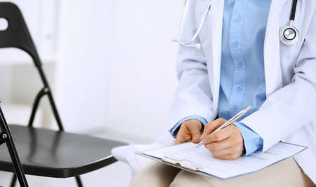 Female doctor writing up medication history records form on clipboard, while sitting at the chair. Physician at work in hospital or clinic. Healthcare, insurance and medicine concept Stockfoto