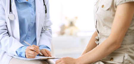 Doctor and patient talking. Physician at work in hospital while writing up medication history records form on clipboard near sitting woman. Healthcare and medicine concepts