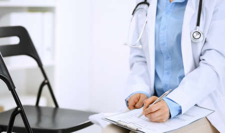 Female doctor writing up medication history records form on clipboard, while sitting at the chair. Physician at work in hospital or clinic. Healthcare, insurance and medicine concept Stock Photo