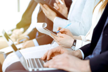 Business people working at meeting or conference, close-up of hands. Group of unknown businessmen and women in modern white office. Teamwork or coaching concept