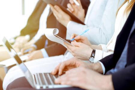 Mensen uit het bedrijfsleven werken op vergadering of conferentie, close-up van handen. Groep onbekende zakenlieden en vrouwen in modern wit kantoor. Teamwerk of coaching concept Stockfoto