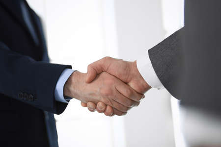 Business people shaking hands at meeting or negotiation in modern office, close-up. Teamwork, partnership and handshake concept Stockfoto