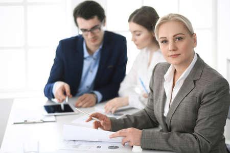 Colpo in testa di una donna d'affari alla negoziazione. Gruppo di uomini d'affari che discutono di domande alla riunione in un ufficio moderno. Lavoro di squadra, partnership e concetto di business